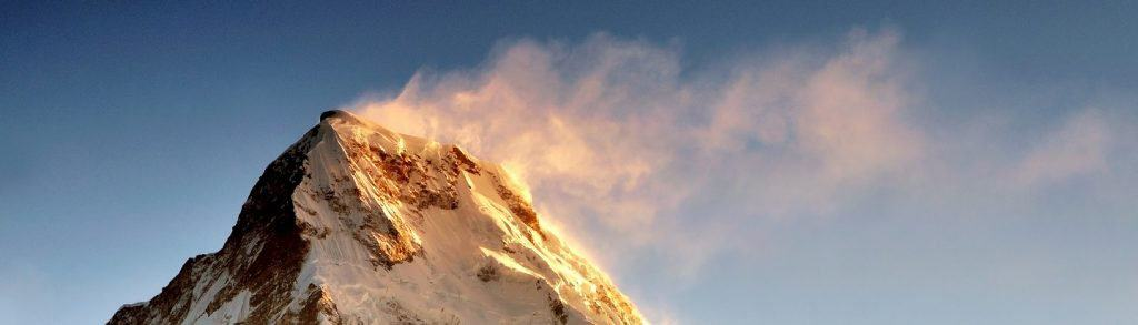 """Dramatic sun light sunrise over snow capped mountain Machapuchare Fish Tail mountain in Annapurna Himalaya, taken during trekking to Poon Hill Nepal. Machhapuchchhre or Machhapuchhre Lit. """"Fish Tail"""" in English, is a mountain in the Annapurna Himal of north central Nepal"""
