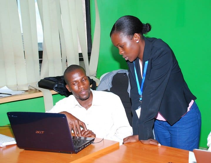 two african workers looking at a laptop screen