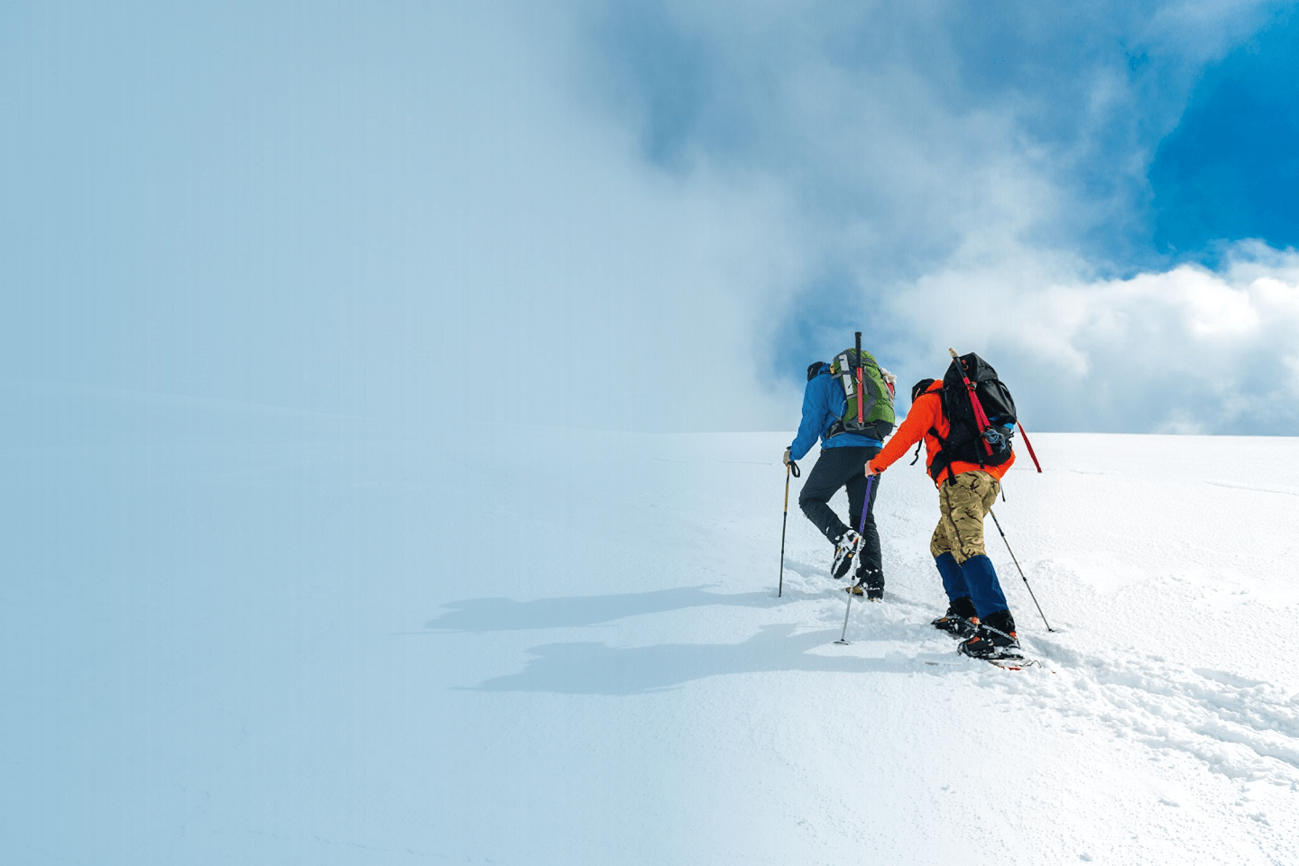 Two mountaineers walking through the mountains covered with snow