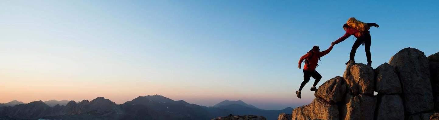 mountain climber helping other mountain climber reach mountain peak