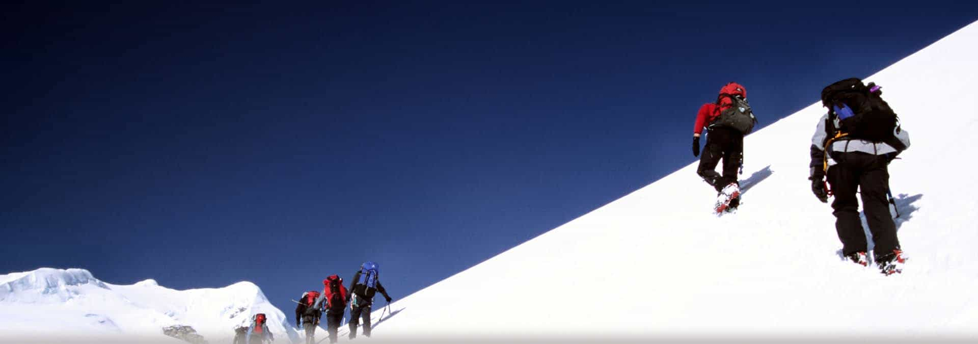hikers climbing snow-covered mountain
