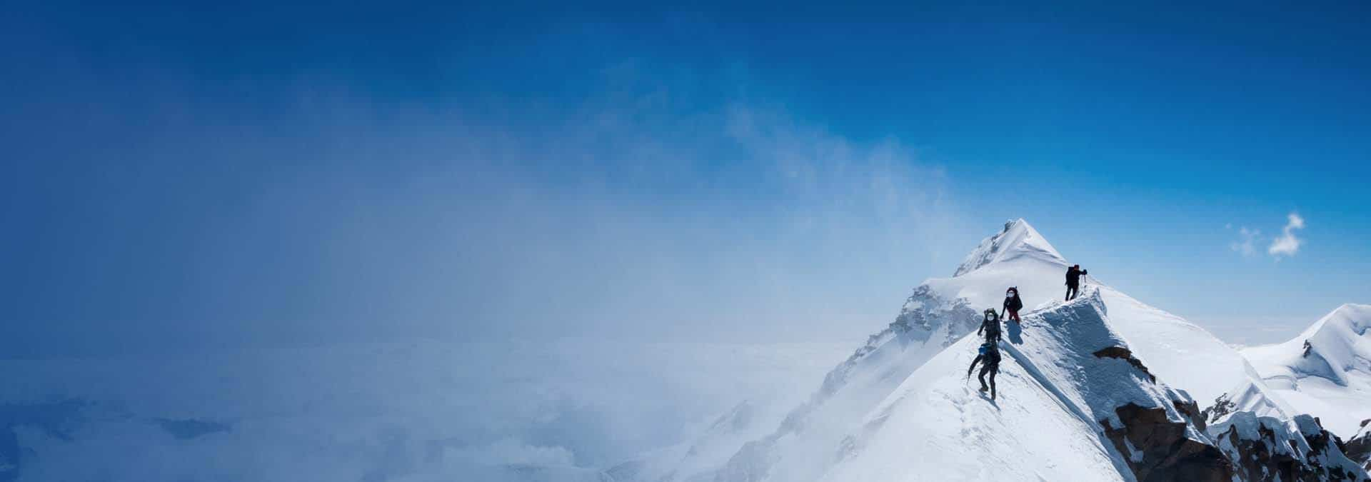 snow-covered mountain with climbers near the top