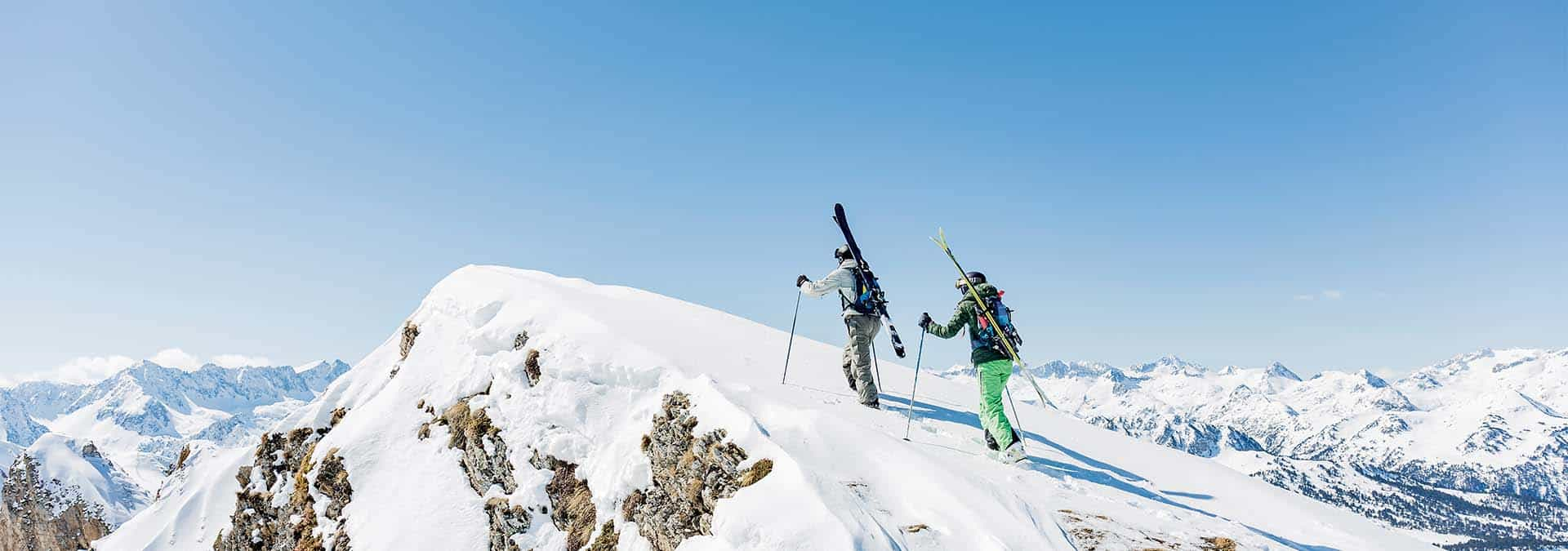 cross-country skiers going up snow-covered mountain