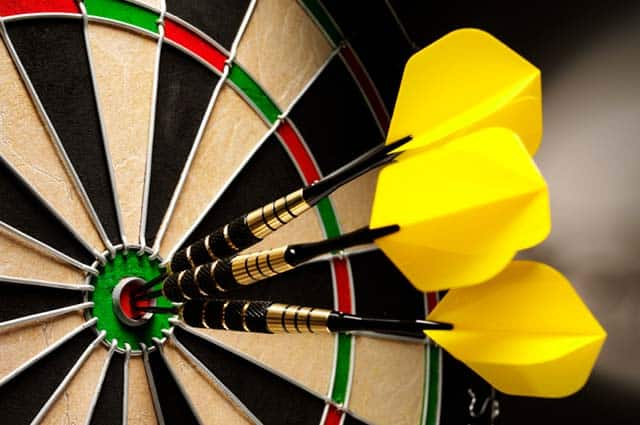 yellow darts in the bullseye of a target