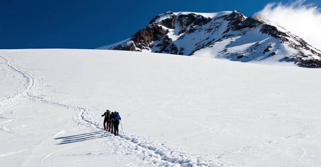 Hikers climbing up snow-covered mountain